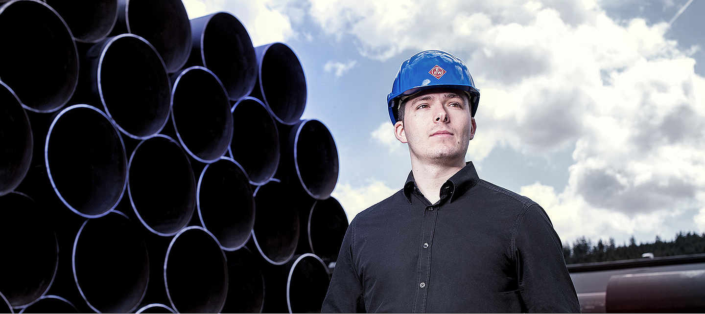 A young employee with branded EEW helmet stands in front of pipes