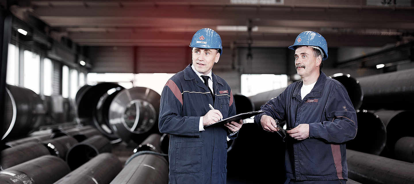 Two employees in EEW workwear with a clipboard standing in an industrial hall