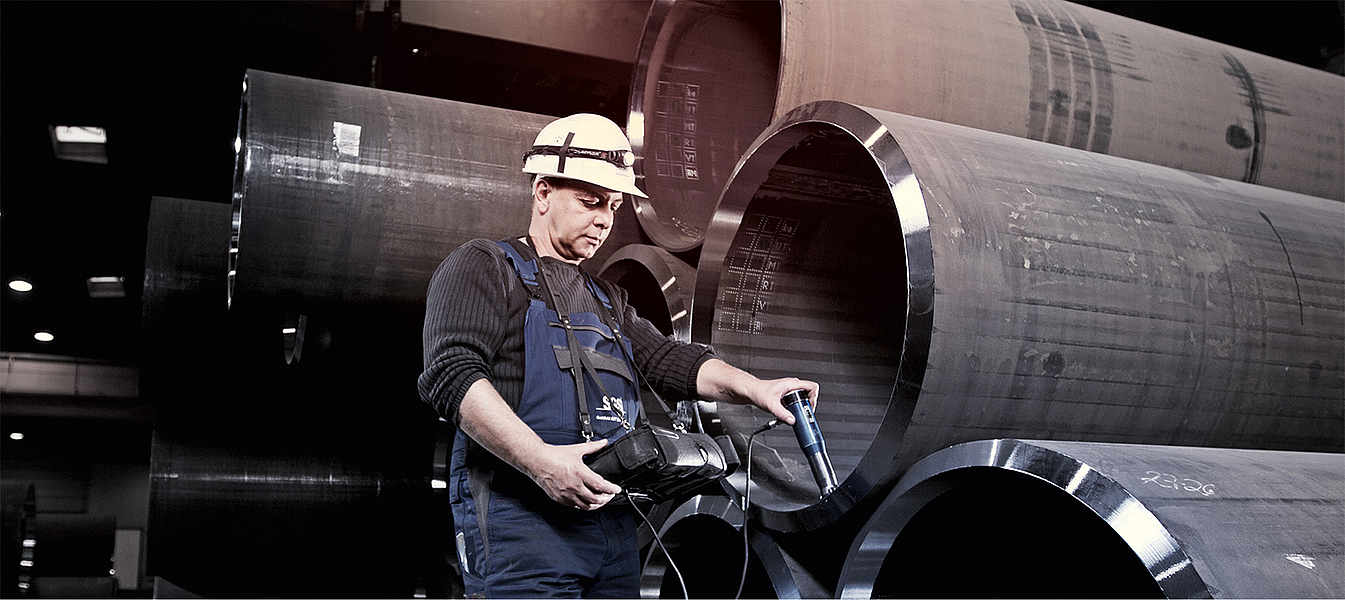 Employee taking measurements of a pipe