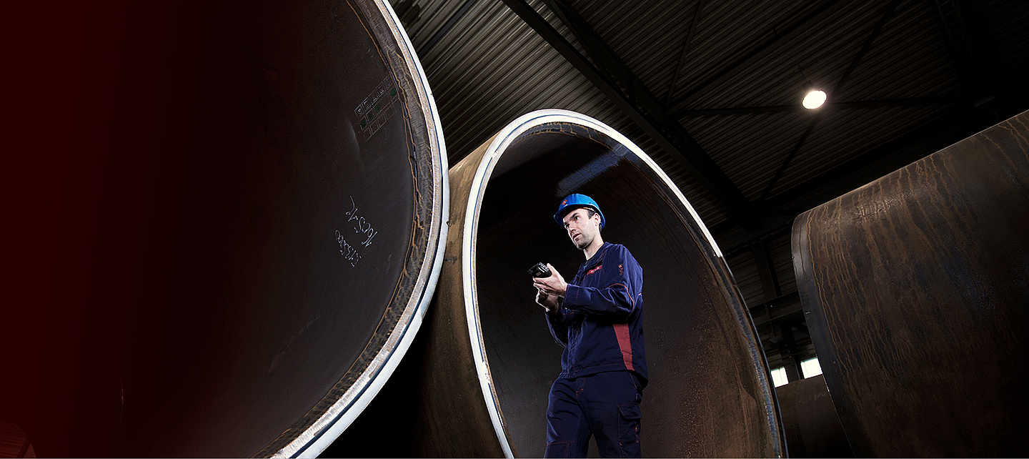 A concentrating man standing between big steel pipes