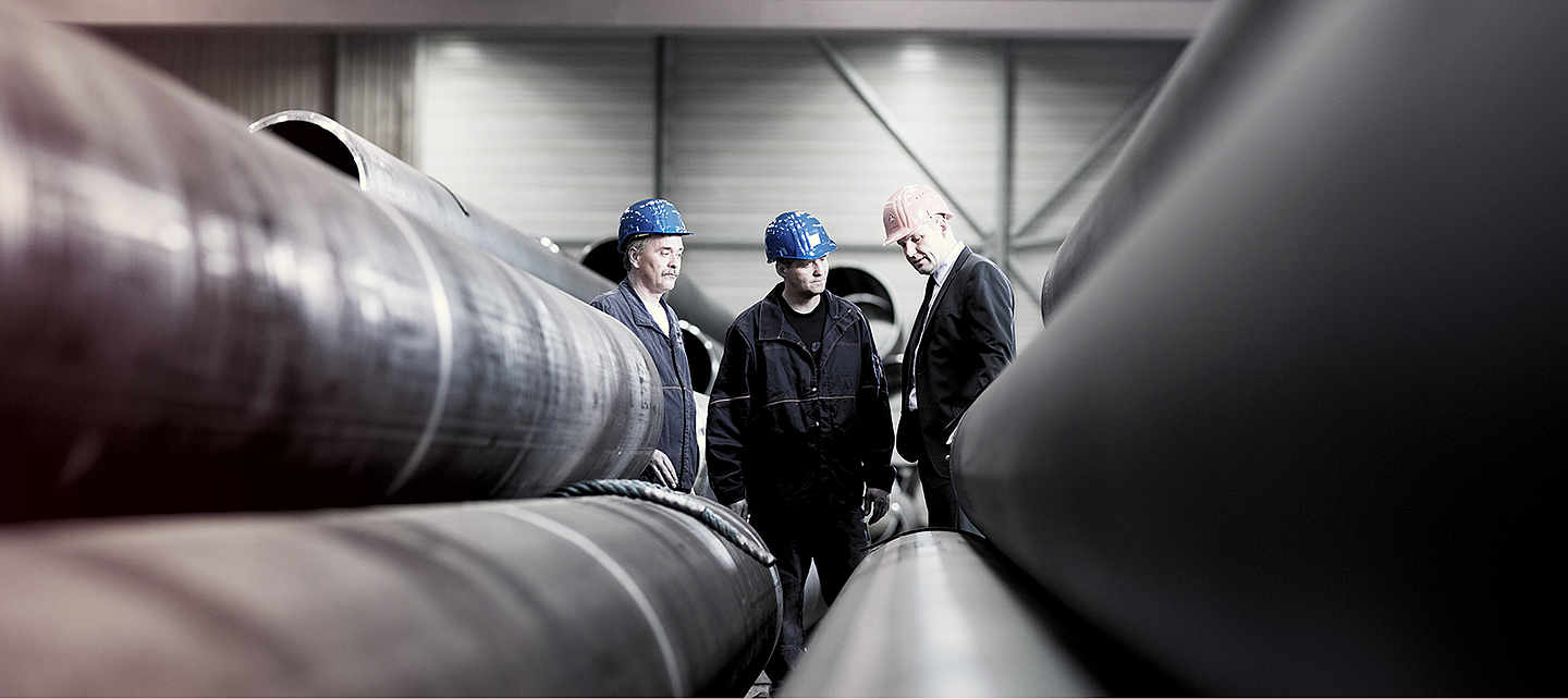 Three men with helmets standing between some metal pipes.