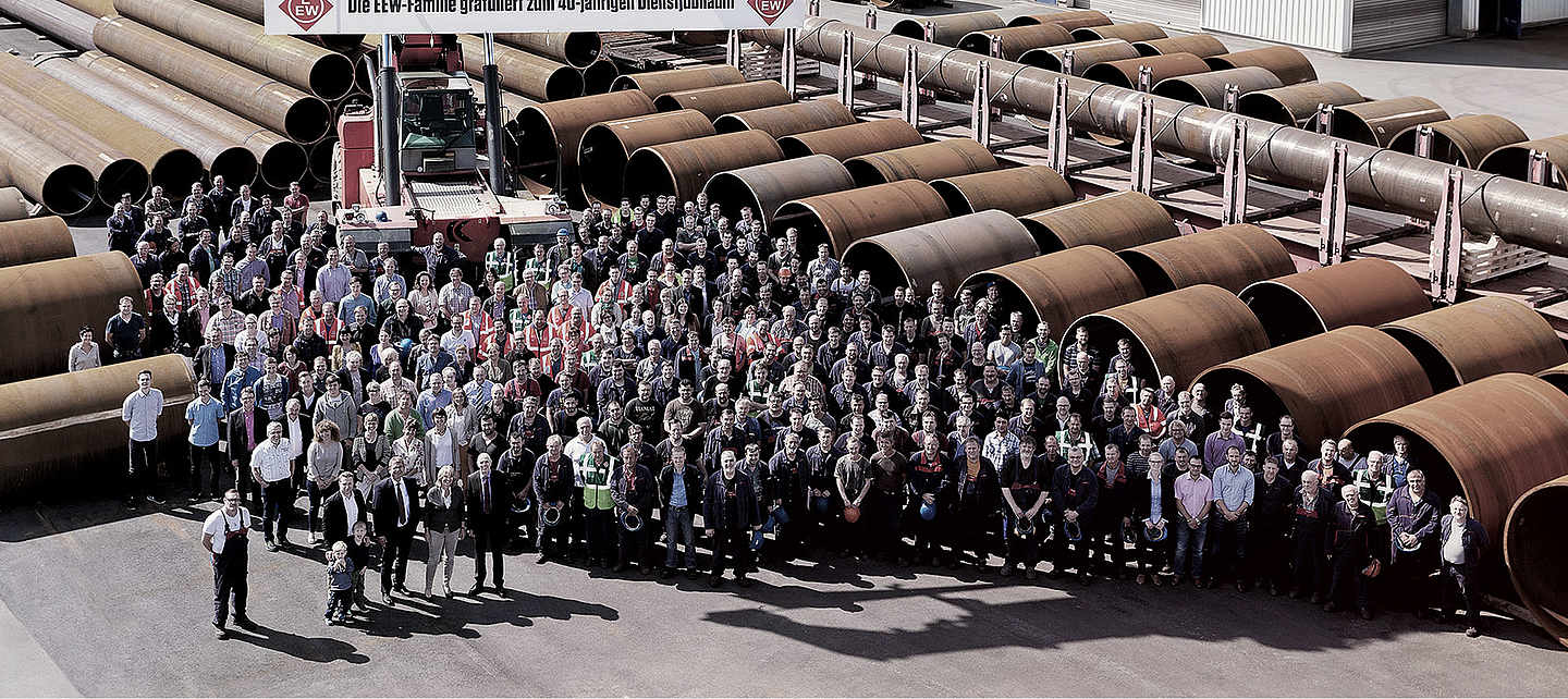 A big team of EEW standing in front of stored pipes