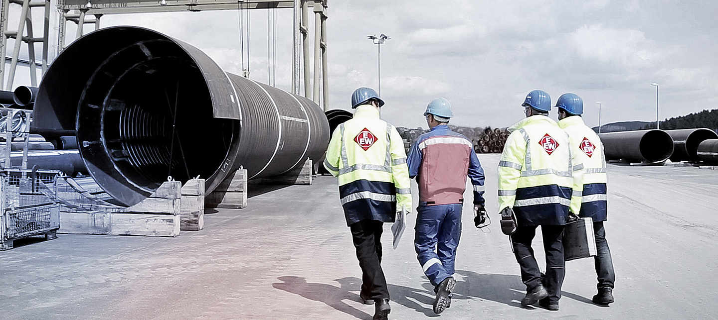 Constuction crew in branded EEW workwear walking towards a big pipe on a construction site