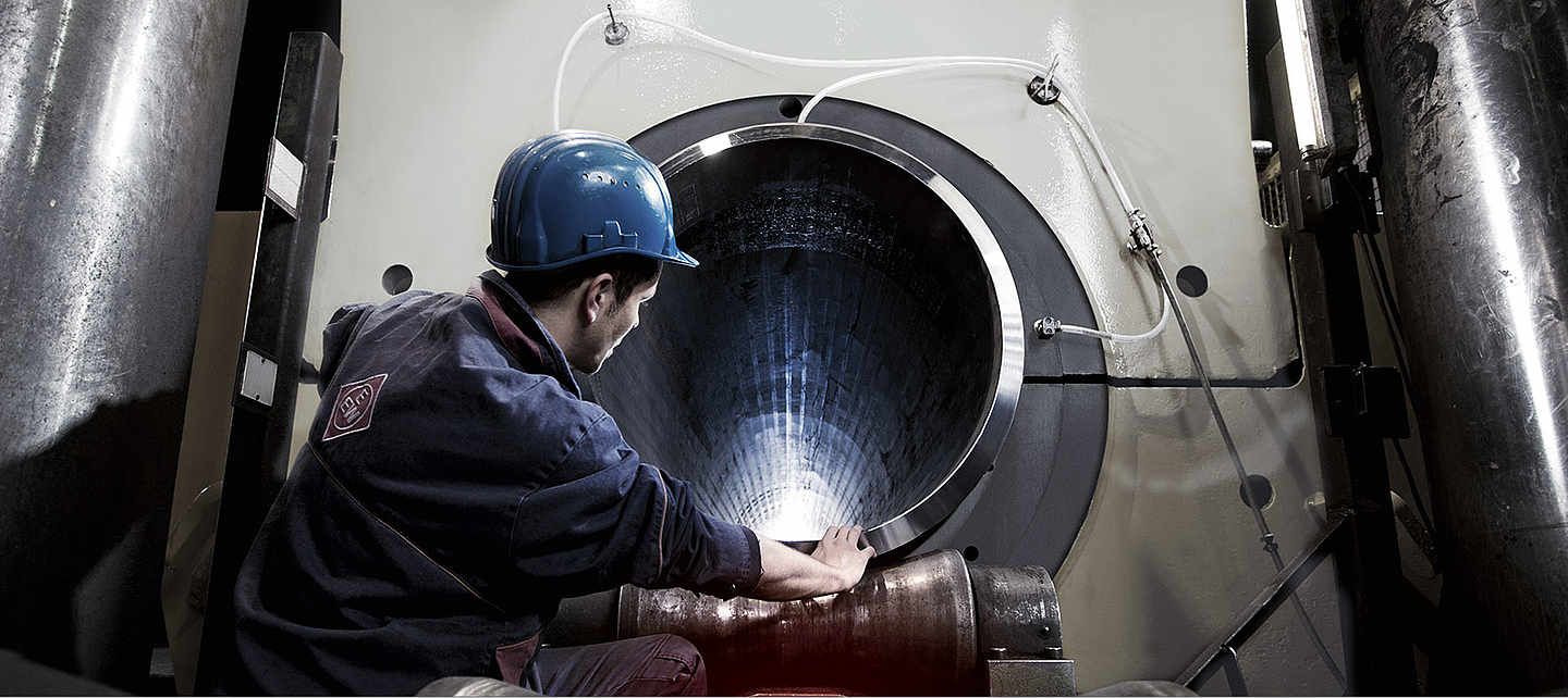 An Employee looking at a big pipe inside a machine