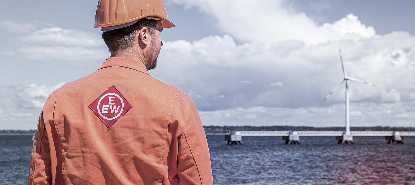 A man with helmet and EEW branded workwear looks at an offshore wind power plant