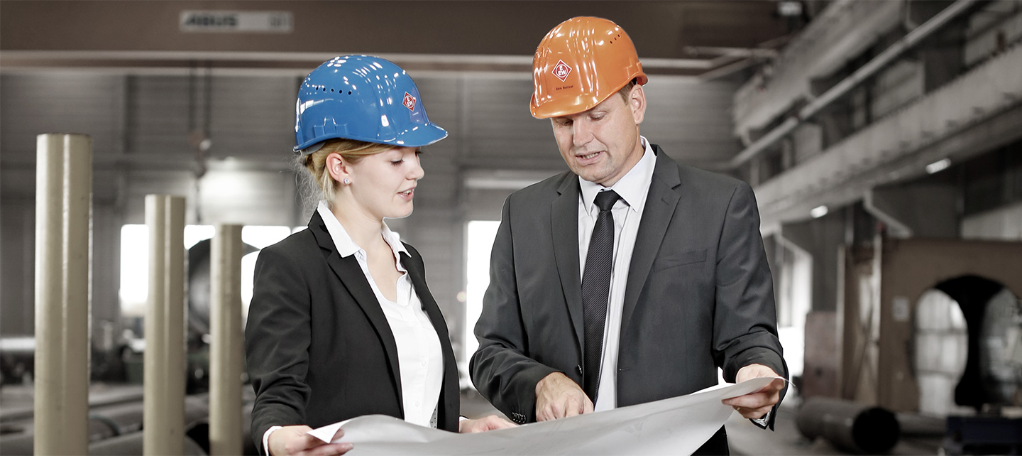 A male and a female employee with branded EEW helmets and suits looking at a blueprint an talk to each other